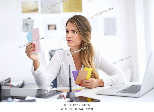 Young woman looking at notes at desk in office