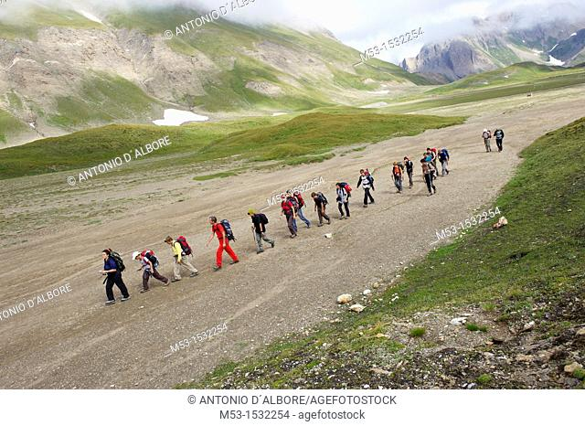A group of hikers in line formation cross the plateau called Piano dei Camosci, Lepontine Alps  Formazza  Italy