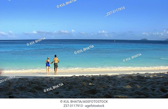 Beach, Mahe, the Seychelles. A mature man and a woman going into the water on a blue-sky day