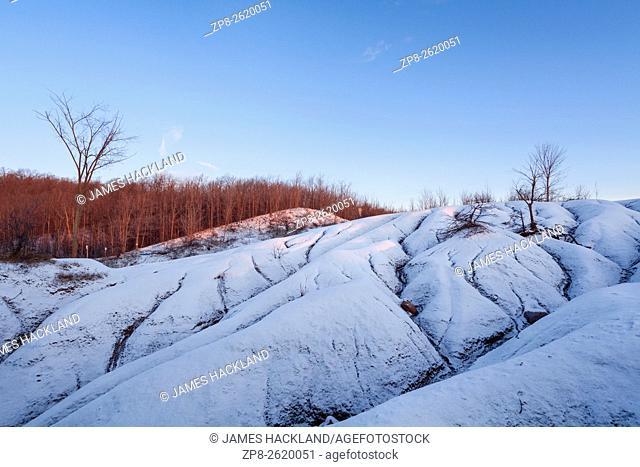 The sun rising on the Cheltenham Badlands covered in a fresh snowfall. Caledon, Peel Region, Ontario, Canada