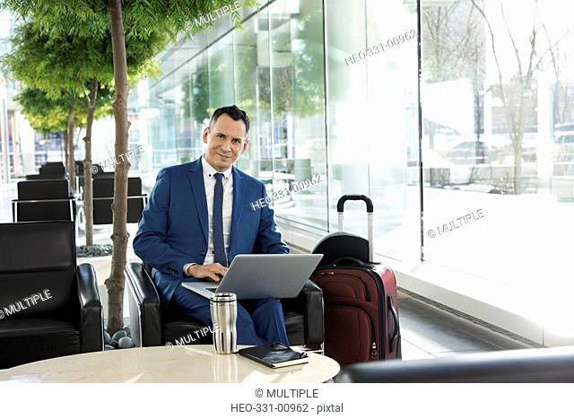 Portrait confident businessman with suitcase working at laptop in airport atrium lounge