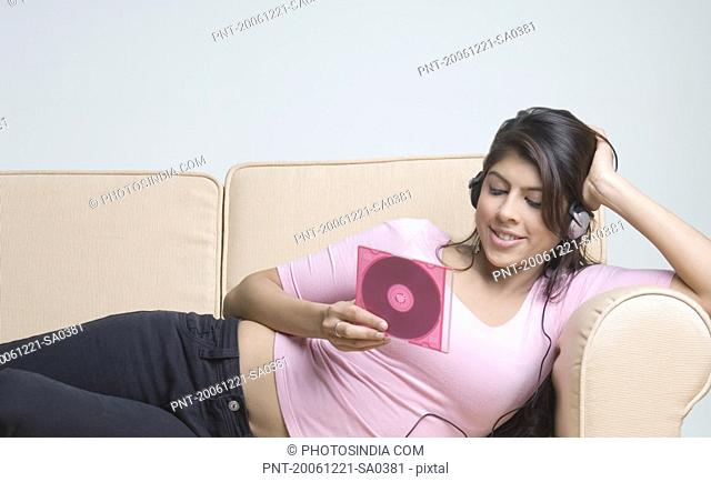 Young woman listening to music and holding a CD case