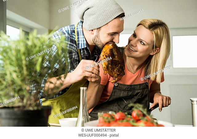 Coupleg in kitchen eating steak from frying pan