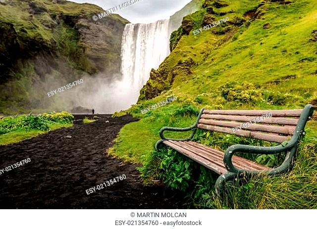 Landscape view of wild Skogafoss waterfall and bench