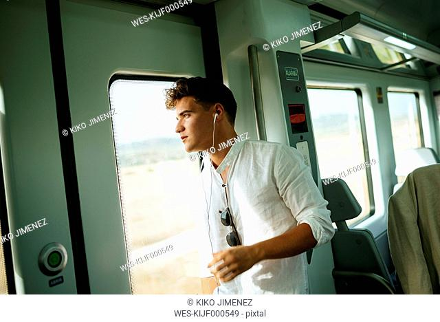 Young man looking out the door on a train