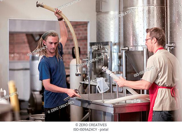 Colleagues in microbrewery holding plastic tubes