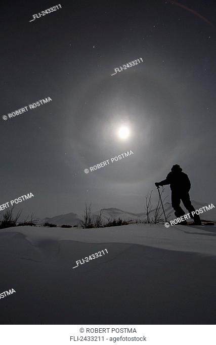 Man snowshoeing along the Dempster Highway under a moon glowing with rings; Yukon, Canada