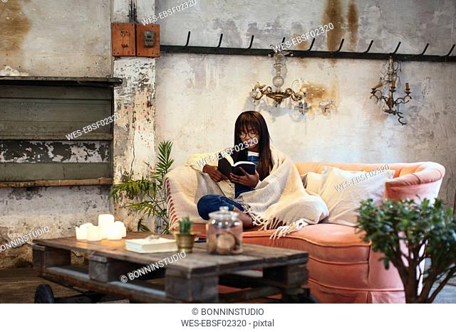Young woman sitting on the couch at home reading book