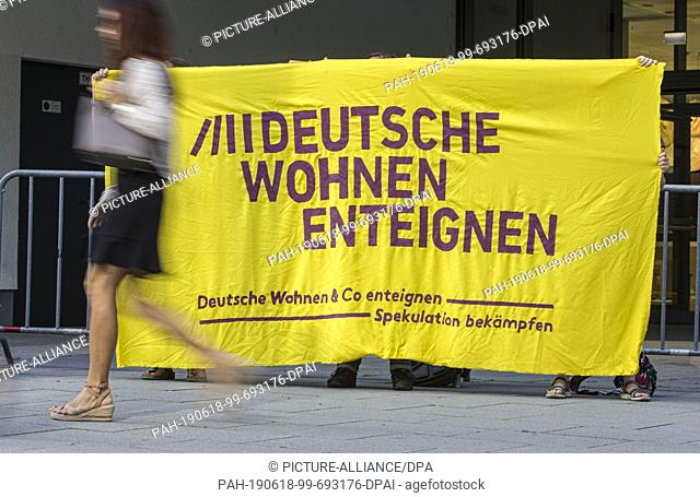 "18 June 2019, Hessen, Frankfurt/Main: In the morning, demonstrators hold a banner with the inscription """"Expropriate German housing"""" in front of the entrance..."