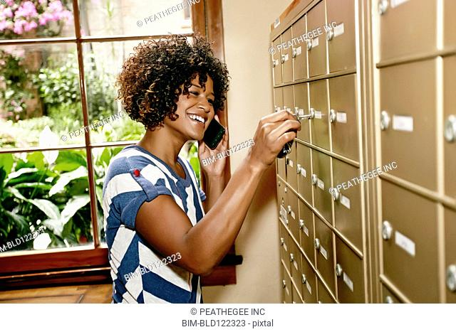 Mixed race woman checking mailbox