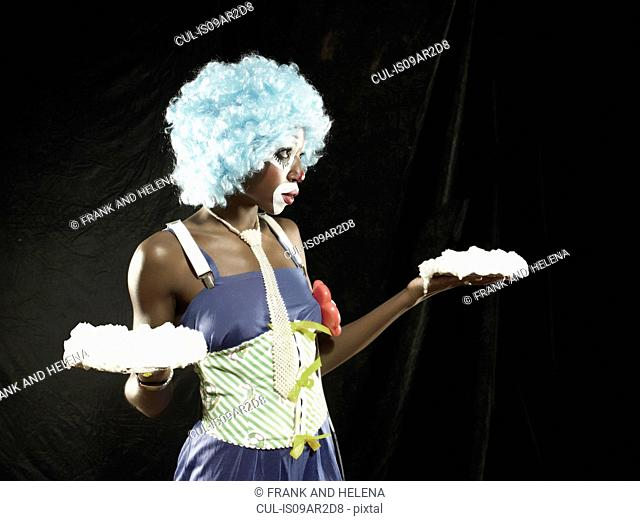 Studio portrait of young woman wearing clown face paint and blue wig holding meringues