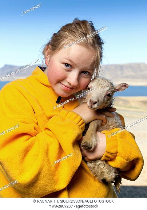 Young girl holding a newborn lamb, Iceland