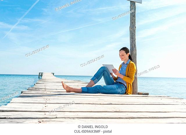 Mid adult woman relaxing on pier, using digital tablet, smiling
