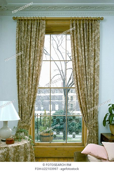 Patterned curtains at sash window with view of the street