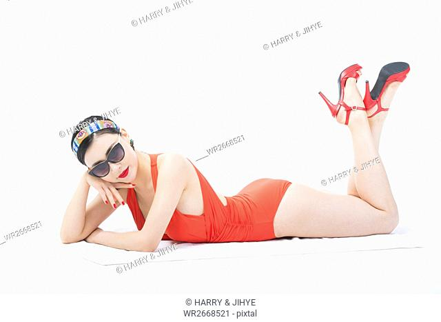 Young woman in swimsuit and sunglasses posing lying face down