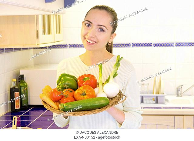 Woman holding vegetable plate in kitchen