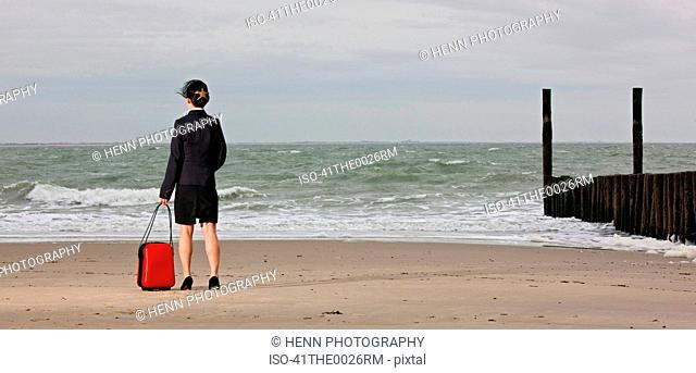 Businesswoman rolling luggage on beach