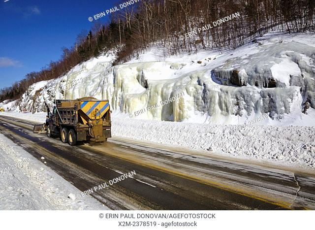 Snow plow truck on Route 112 in Kinsman Notch of Woodstock, New Hampshire USA during the winter months