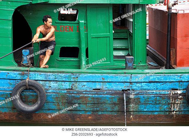 Fisherman mooring his boat at Bungus Port, Padang, West Sumatra, Indonesia