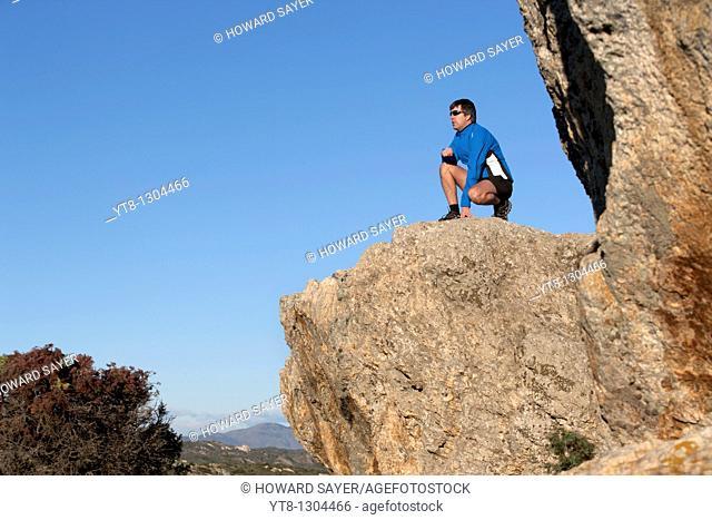 Man kneeling on a rock ledge