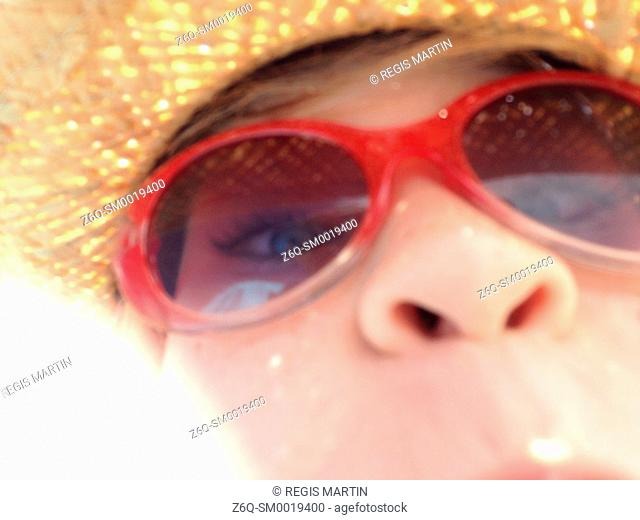 Closeup of a young girl wearing a straw hat and sunglasses