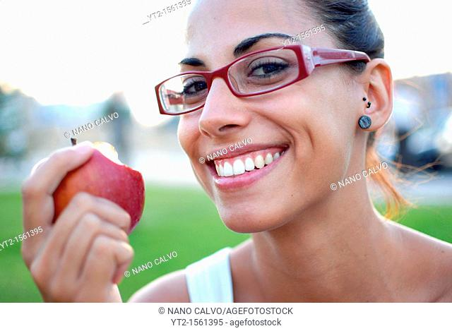 Young woman eating a red apple in nature