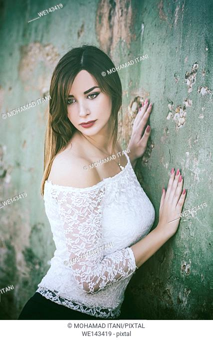 Beautiful young woman leaning against the wall looking away