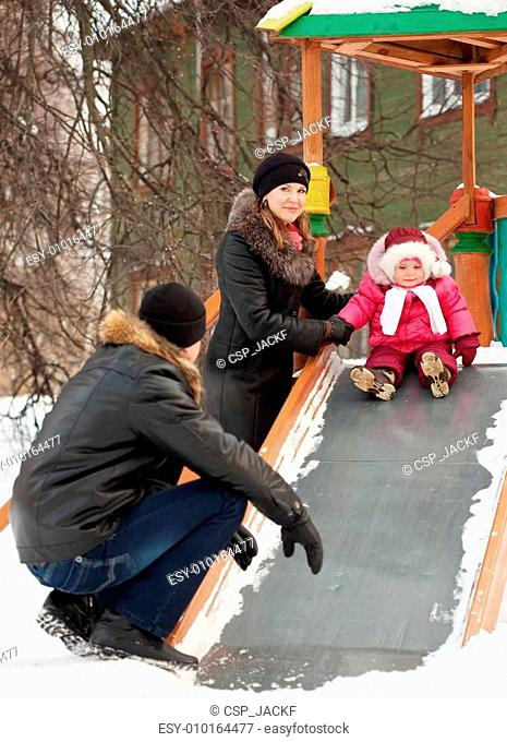 parents with toddler playing on slide