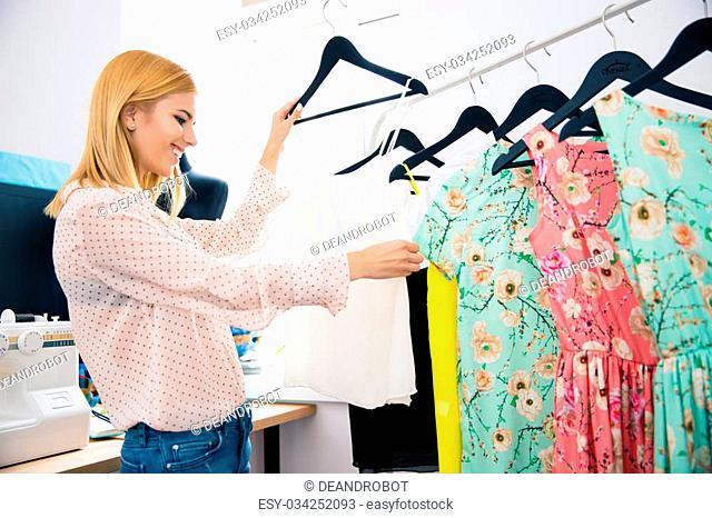 Smiling fashion designer looking on dresses in workshop