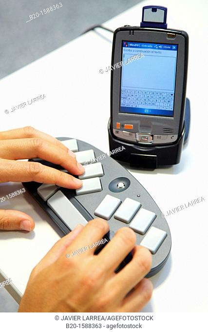 Person labeling a music CD using the braille BlueType keyboard  The person writes the information using the braille bluetooth BlueType keyboard  Later