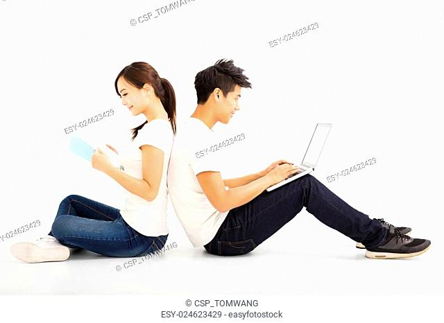 Happy young students couple with laptop and book
