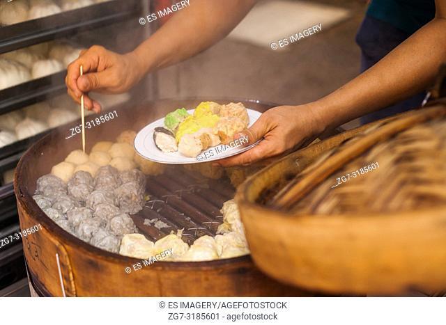 A street vendor prepares steamed Dim Sum (Shumai/Shaomai) in the Jalan Petaling street market, Chinatown, Kuala Lumpur