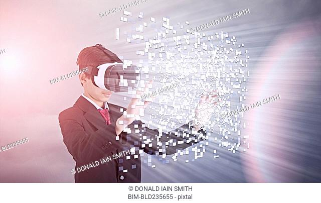 Mixed Race boy wearing suit using vr goggles