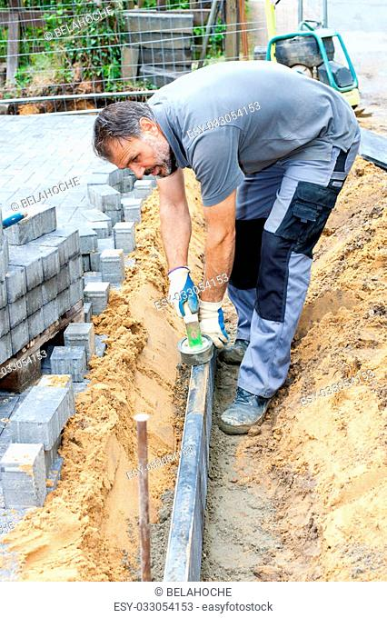 Construction worker puts stone slabs to mark a property and separate private property from street