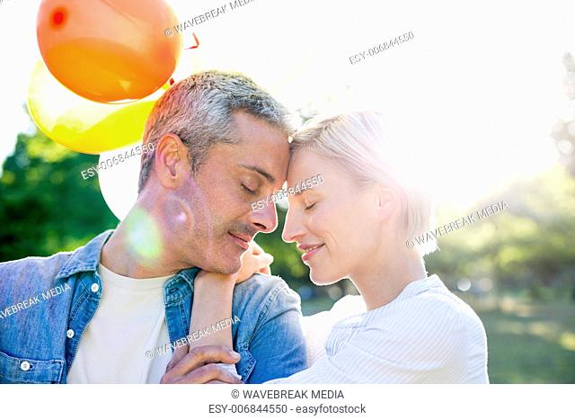 Cute couple holding balloons at the park