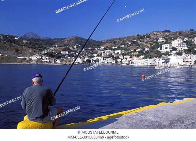 Man fishing on the port of Armenistis and view of houses Ikaria, Northeastern Aegean Island, Greece