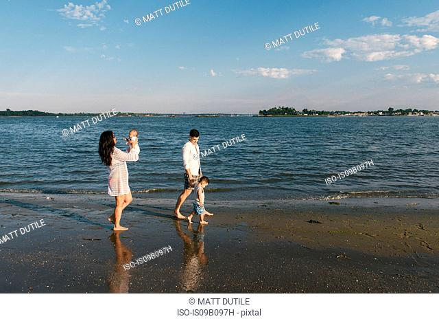 Parents with baby and toddler son strolling by sea, Pelham Bay Park, Bronx, New York, USA
