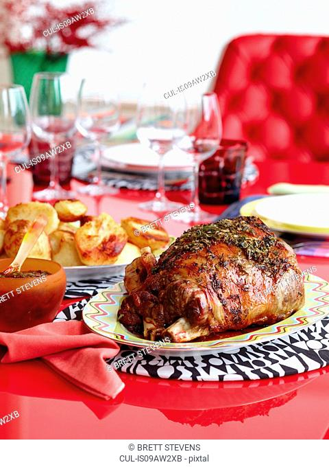 Joint of lamb on platter with roasted potatoes
