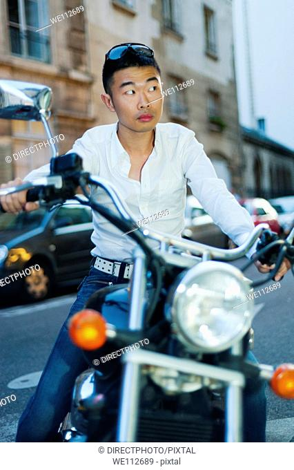 Paris, France, Young Asian Man Sitting on Vintage Motorcycle on Street in St. Germain des Prés District