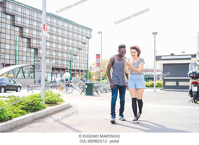 Couple in urban area looking at smartphone, Milan, Italy