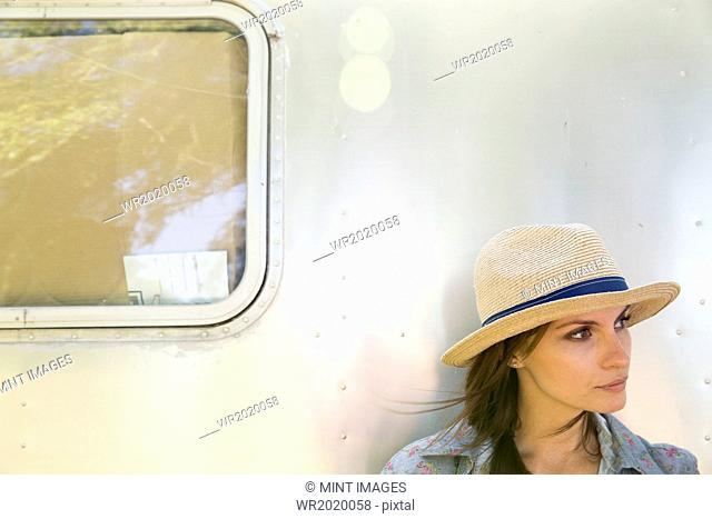 A young woman wearing a hat sitting in the shade of a silver coloured trailer