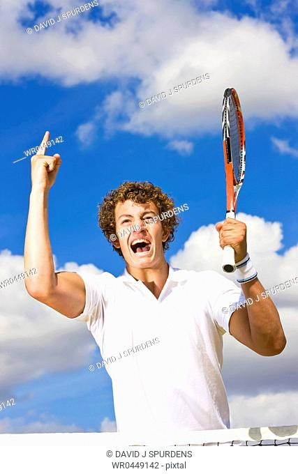 A tennis player celebrates game set and match