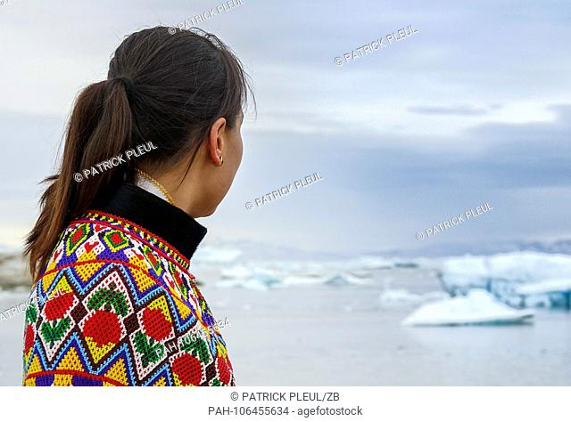 21.06.2018, Gronland, Denmark: A young woman in a national costume is standing on July 21st in the coastal town of Ilulissat in western Greenland