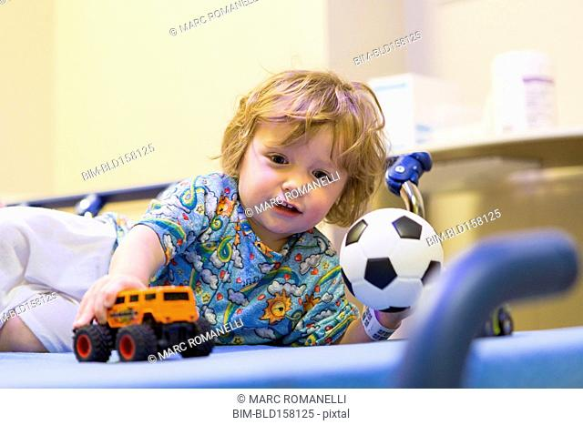 Caucasian boy playing on hospital bed