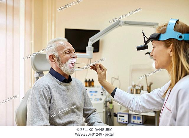ENT physician examining mouth of a senior man