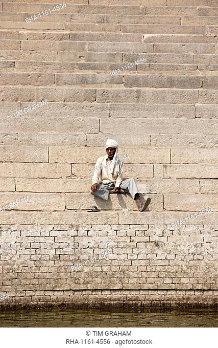 Hindu man sits on steps of Chet Singh Ghat on banks of The Ganges River in holy city of Varanasi, India
