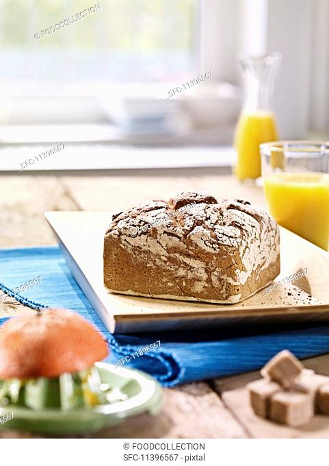 A square loaf of rye bread on a flat wooden tray