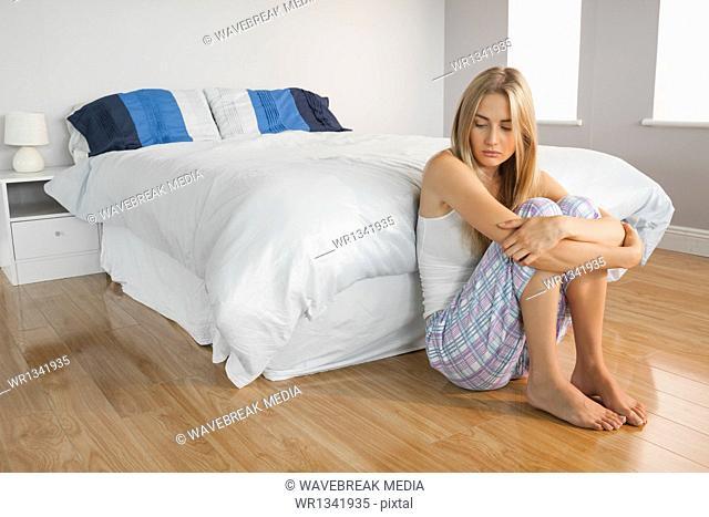 Depressed blonde sitting on the floor