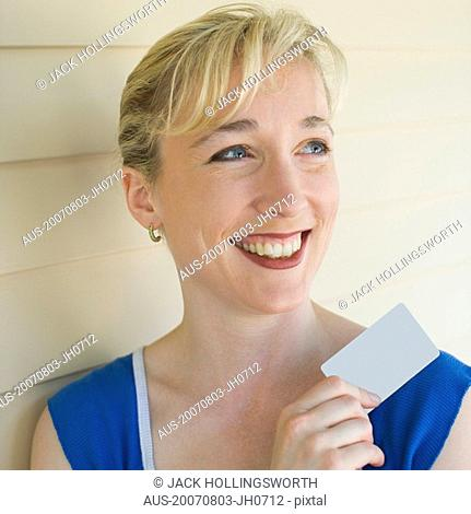 Close-up of a mid adult woman holding a credit card and smiling
