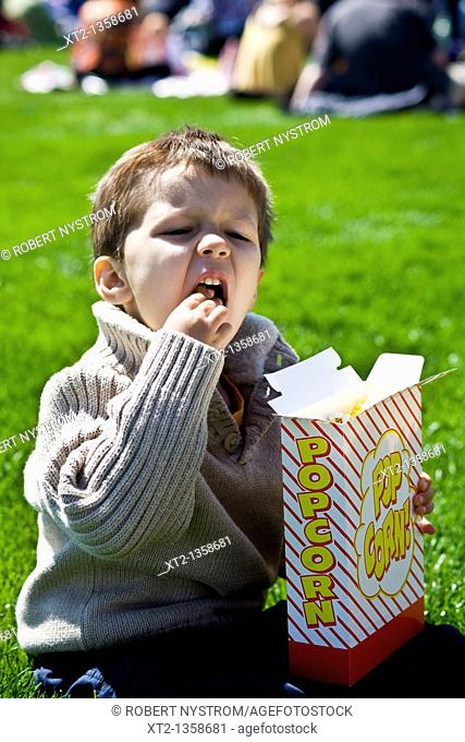 Little boy sitting in a grassy park eating popcorn